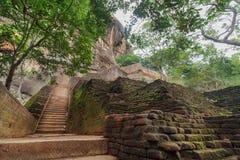 Σκαλοπάτια πετρών Grunge στον αρχαίο βράχο Sigiriya με τη archeological περιοχή, Σρι Λάνκα Περιοχή παγκόσμιων κληρονομιών της ΟΥΝ Στοκ Φωτογραφία