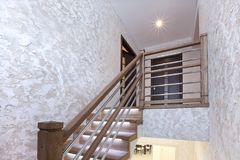 Σκαλοπάτια της βαλανιδιάς με το φωτισμό και του διακοσμητικού ασβεστοκονιάματος στους τοίχους στοκ εικόνα