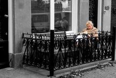Σκανδιναβικός υπαίθριος τρόπος ζωής, όμορφη ηλικιωμένη ξανθή γυναίκα που διαβάζει ένα βιβλίο σε ένα μπαλκόνι, Άμστερνταμ