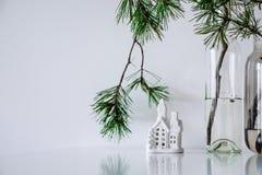 Σκανδιναβικό ντεκόρ Χριστουγέννων κλάδοι πεύκων και ένα κεραμικό σπίτι στοκ εικόνες