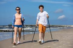 Σκανδιναβικό περπάτημα - νέοι που επιλύουν στην παραλία στοκ εικόνες
