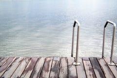 Σκαλοπάτια στη θάλασσα ή τη λίμνη και την ξύλινη γέφυρα Στοκ Εικόνες