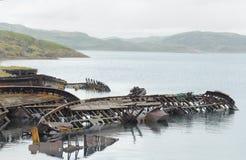 Σκελετός βαρκών grunge που θάβεται κατά το ήμισυ στη θάλασσα Θάλασσα Barents Σκάφος grav Στοκ Εικόνες