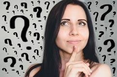 Σκεπτικά νέα γυναίκα και μέρη των ερωτηματικών στοκ εικόνες