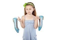 Σκεπτικές στάσεις κοριτσιών, που κρατούν τα μεγάλα παπούτσια μητέρων Στοκ Φωτογραφίες