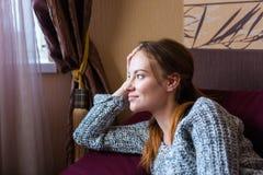 Σκεπτική αρκετά νέα γυναίκα που βρίσκεται στον καναπέ στο καθιστικό Στοκ Φωτογραφίες