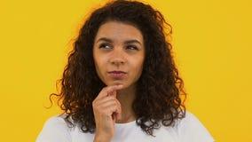 Σκεπτική αφρικανική γυναίκα στη φωτεινή σκέψη υποβάθρου την επιλογή, ονειρεμένος πρόσωπο απόθεμα βίντεο