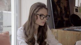 Σκεπτική επιχειρηματίας που κοιτάζει μακριά για την ιδέα χρησιμοποιώντας το lap-top με τον καφέ στον καφέ απόθεμα βίντεο