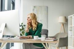 σκεπτική επιχειρηματίας που κοιτάζει μακριά χρησιμοποιώντας τον υπολογιστή γραφείου Στοκ Εικόνα