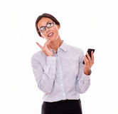 Σκεπτική επιχειρηματίας brunette με το τηλέφωνο κυττάρων Στοκ φωτογραφία με δικαίωμα ελεύθερης χρήσης