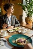 Σκεπτική ευφυής επιχειρησιακή κυρία που τρώει τη σαλάτα στον καφέ στοκ εικόνα