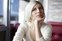 Σκεπτική και στοχαστική νέα γυναίκα στον καφέ στοκ φωτογραφίες