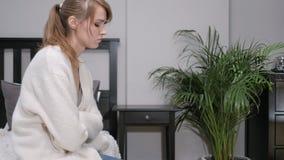 Σκεπτική λυπημένη συνεδρίαση γυναικών στην πλευρά του κρεβατιού στοκ εικόνες με δικαίωμα ελεύθερης χρήσης