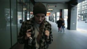 Σκεπτική νέα γυναίκα μόδας με το σακίδιο πλάτης που περπατά στην πόλη, steadicam πυροβολισμός απόθεμα βίντεο