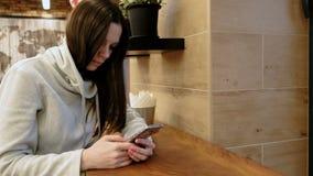 Σκεπτική νέα γυναίκα brunette σε ένα φωτεινό πουκάμισο που χρησιμοποιεί Διαδίκτυο στη συνεδρίαση κινητών τηλεφώνων της στον καφέ απόθεμα βίντεο