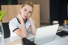 σκεπτική νέα επιχειρηματίας που κοιτάζει μακριά καθμένος στον πίνακα με το lap-top Στοκ φωτογραφία με δικαίωμα ελεύθερης χρήσης