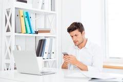Σκεπτική νέα συνεδρίαση επιχειρηματιών στον πίνακα και χρησιμοποίηση του smartphone Στοκ Φωτογραφία