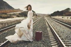 Σκεπτική νύφη με μια κόκκινη βαλίτσα στοκ εικόνες