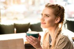 Σκεπτική δοκιμάζοντας κούπα κοριτσιών του καυτού ποτού Στοκ Εικόνες