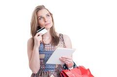 Σκεπτική πανέμορφη κυρία με την πιστωτική κάρτα και τη σύγχρονη ταμπλέτα Στοκ Φωτογραφία