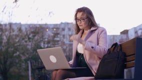 Σκεπτική όμορφη νέα γυναίκα που εργάζεται στο lap-top στο πάρκο πόλεων το βράδυ φιλμ μικρού μήκους