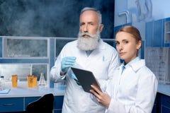 Σκεπτικοί εργαστηριακοί τεχνικοί στα παλτά εργαστηρίων που εξετάζουν τη κάμερα Στοκ Εικόνες