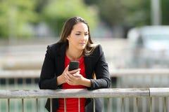 Σκεπτικός ανώτερος υπάλληλος που κρατά ένα τηλέφωνο υπαίθρια Στοκ εικόνες με δικαίωμα ελεύθερης χρήσης