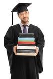 Σκεπτικός απόφοιτος φοιτητής που κρατά έναν σωρό των βιβλίων Στοκ εικόνα με δικαίωμα ελεύθερης χρήσης