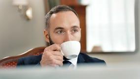 Σκεπτικός αρσενικός επιχειρηματίας πορτρέτου που έχει το τσάι ή τον καφέ κατανάλωσης σπασιμάτων φιλμ μικρού μήκους