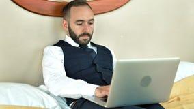Σκεπτικός αρσενικός επιχειρηματίας που βρίσκεται στο κρεβάτι στο δωμάτιο ξενοδοχείου που χρησιμοποιεί το PC lap-top που λειτουργε φιλμ μικρού μήκους