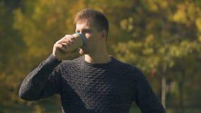 Σκεπτικός αρσενικός καφές κατανάλωσης στο πάρκο φθινοπώρου, που σκέφτεται για το ξεκίνημα, στόχοι απόθεμα βίντεο