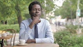 Σκεπτικός αφρικανικός επιχειρηματίας που σκέφτεται καθμένος στον υπαίθριο καφέ φιλμ μικρού μήκους