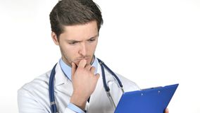 Σκεπτικός γιατρός που διαβάζει τα ιατρικά έγγραφα που απομονώνονται στο άσπρο υπόβαθρο απόθεμα βίντεο