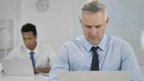 Σκεπτικός γκρίζος επιχειρηματίας τρίχας που σκέφτεται και που εργάζεται στο lap-top φιλμ μικρού μήκους