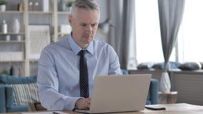 Σκεπτικός γκρίζος επιχειρηματίας τρίχας που σκέφτεται και που εργάζεται στο lap-top απόθεμα βίντεο