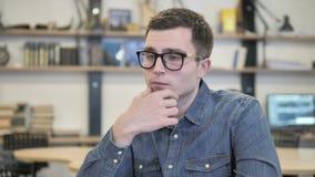 Σκεπτικός δημιουργικός νεαρός άνδρας που σκέφτεται μια ιδέα φιλμ μικρού μήκους
