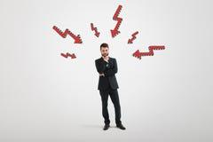 Σκεπτικός επιχειρηματίας με τα κόκκινα arows που δείχνουν σε τον Στοκ Εικόνα