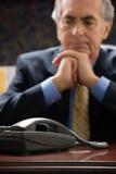 Σκεπτικός επιχειρηματίας με το τηλέφωνο Στοκ Φωτογραφία