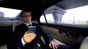 Σκεπτικός επιχειρηματίας που γράφει το ηλεκτρονικό ταχυδρομείο, που οδηγά στο αυτοκίνητο, αγχωτική εργασία, workaholic στοκ φωτογραφία με δικαίωμα ελεύθερης χρήσης