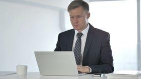 Σκεπτικός επιχειρηματίας που σκέφτεται και που εργάζεται στο lap-top απόθεμα βίντεο