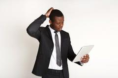 Σκεπτικός επιχειρηματίας που χρησιμοποιεί την ταμπλέτα που απομονώνεται στο λευκό στοκ φωτογραφίες με δικαίωμα ελεύθερης χρήσης