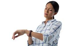 Σκεπτικός θηλυκός ανώτερος υπάλληλος που δείχνει στο wristwatch της Στοκ Εικόνες