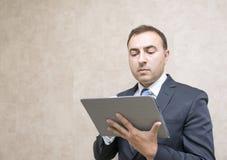 Σκεπτικός και σοβαρός επιχειρηματίας που φαίνεται μήνυμα στην ταμπλέτα comput Στοκ Εικόνα