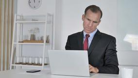 Σκεπτικός μέσος ηλικίας επιχειρηματίας που σκέφτεται και που εργάζεται στο lap-top απόθεμα βίντεο