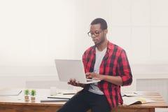 Σκεπτικός μαύρος επιχειρηματίας στο περιστασιακό γραφείο, εργασία με το lap-top Στοκ φωτογραφία με δικαίωμα ελεύθερης χρήσης