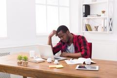 Σκεπτικός μαύρος επιχειρηματίας στο περιστασιακό γραφείο, εργασία με το lap-top Στοκ εικόνες με δικαίωμα ελεύθερης χρήσης