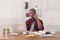 Σκεπτικός μαύρος επιχειρηματίας στο περιστασιακό γραφείο, εργασία με το lap-top Στοκ Εικόνες