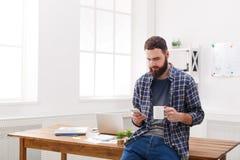 Σκεπτικός νέος αρσενικός επιχειρηματίας που χρησιμοποιεί το τηλέφωνο στην αρχή Στοκ Εικόνες