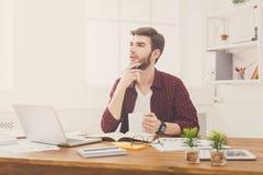 Σκεπτικός νέος επιχειρηματίας με το lap-top στο σύγχρονο άσπρο γραφείο στοκ εικόνες με δικαίωμα ελεύθερης χρήσης