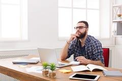 Σκεπτικός νέος επιχειρηματίας που εργάζεται με το lap-top στο σύγχρονο άσπρο γραφείο στοκ εικόνα με δικαίωμα ελεύθερης χρήσης